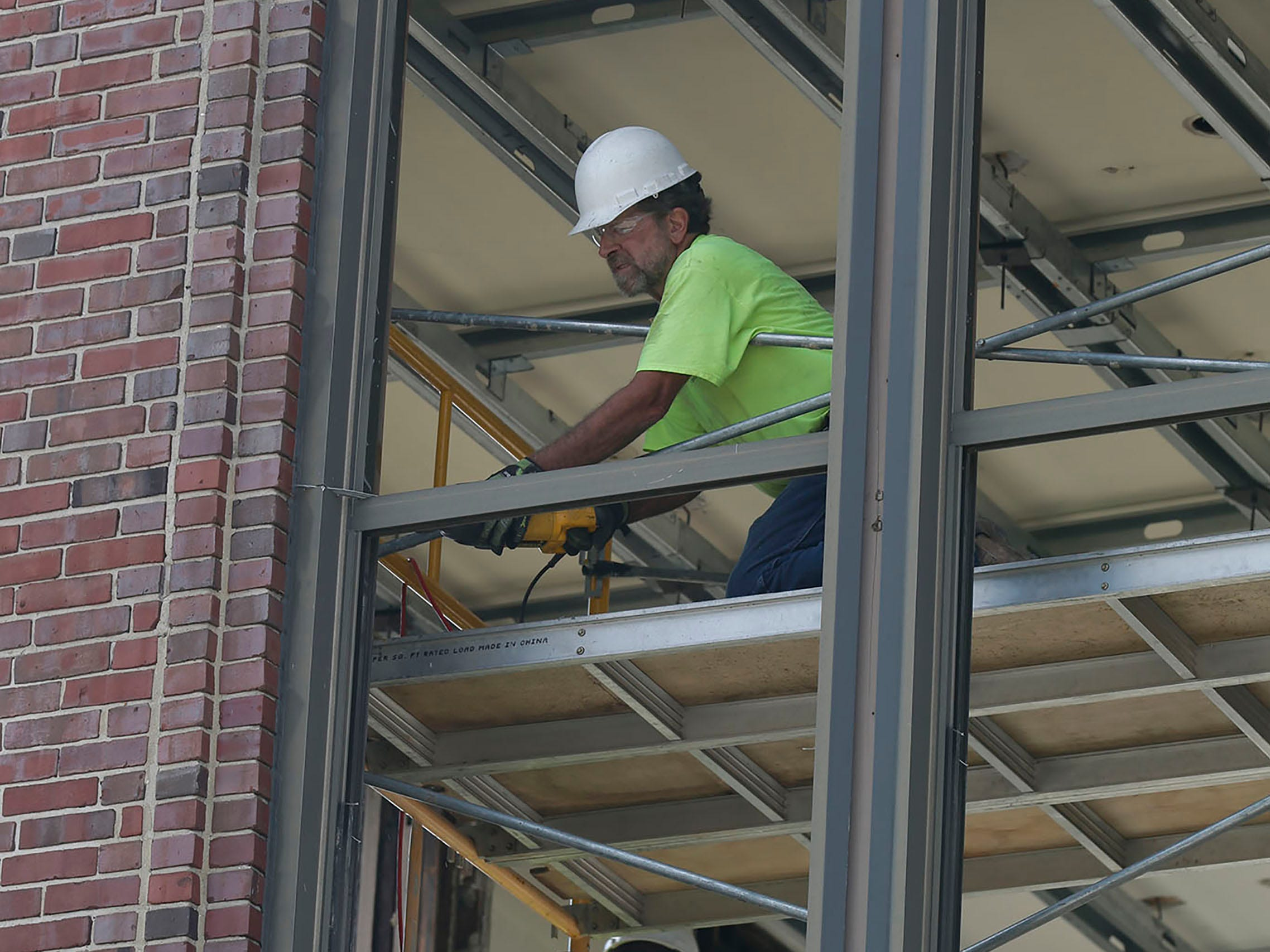 A Quasius employee cuts out an old window frame at Sheboygan City Hall, Tuesday, October 9, 2018, in Sheboygan, Wis. The city is doing a multi-million dollar renovation of the structure.