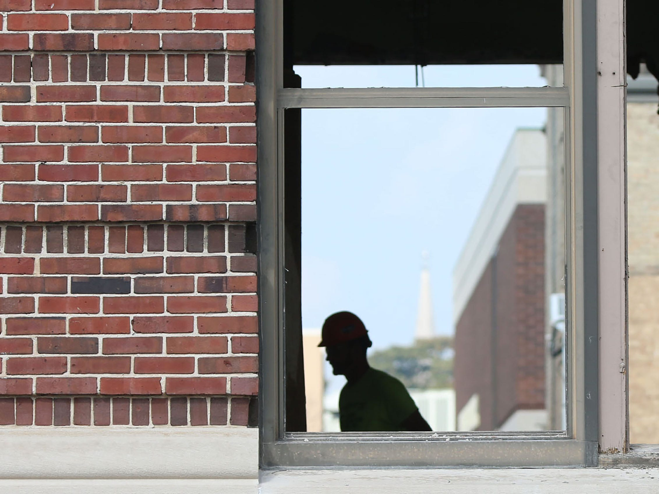 A Quasius employee silhouetted by a window frame at Sheboygan City Hall, Tuesday, October 9, 2018, in Sheboygan, Wis. The city is doing a multi-million dollar renovation of the structure.