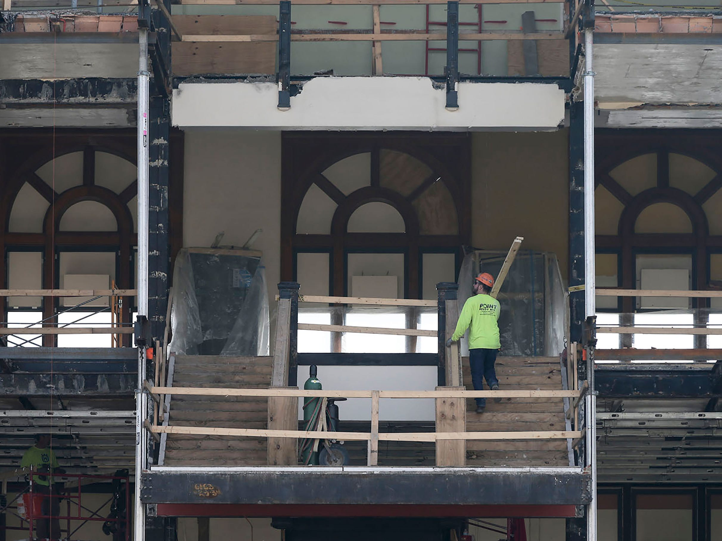 A Quasius worker climbs steps with a board over his shoulder on the north side of Sheboygan City Hall, Tuesday, October 9, 2018, in Sheboygan, Wis. The city is doing a multi-million dollar renovation of the structure.