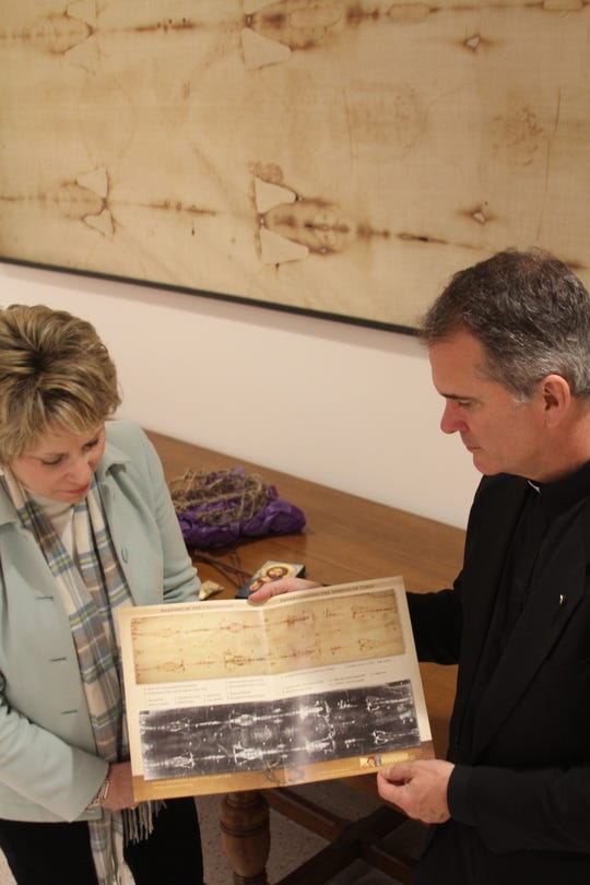 Father  Peter  Mangum  and  Dr.  Cheryl  White  at  the  Regional Shroud  of  Turin  Exhibit  in  the  Parish  Hall  at  the  Cathedral  of  St.  John  Berchmans  in  Shreveport.