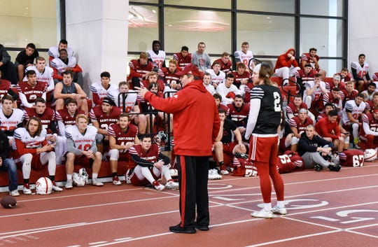 Head coach Gary Fasching tells the team of Jackson Erdmann's accomplishments before he receives the Allstate AFCA Good Works Team award for his volunteer work Tuesday, Oct. 9, after practice at St. John's University.