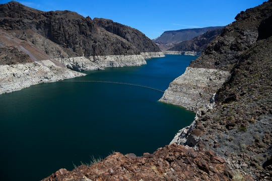 FILE - In this May 31, 2018, file photo, the low level of the water line is shown on the banks of the Colorado River in Hoover Dam, Ariz. Seven Southwestern U.S. states that depend on the overtaxed Colorado River say they have reached tentative agreements on managing the waterway amid an unprecedented drought. The plans announced Tuesday, Oct. 9 were a milestone for the river, which supports 40 million people and 6,300 square miles (16,300 square kilometers) of farmland in the U.S. and Mexico. The plans aren't designed to prevent a shortage, but they're intended to help manage and minimize the problems. (AP Photo/Ross D. Franklin, File)