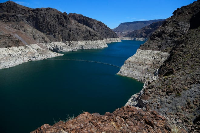 FILE - In this May 31, 2018, file photo, the low level of the water line is shown on the banks of the Colorado River in Hoover Dam, Ariz.