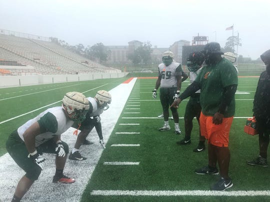 FAMU offensive coordinator/offensive line coach Alex Jackson goes over blocking schemes during the early rainfall of Hurricane Michael.