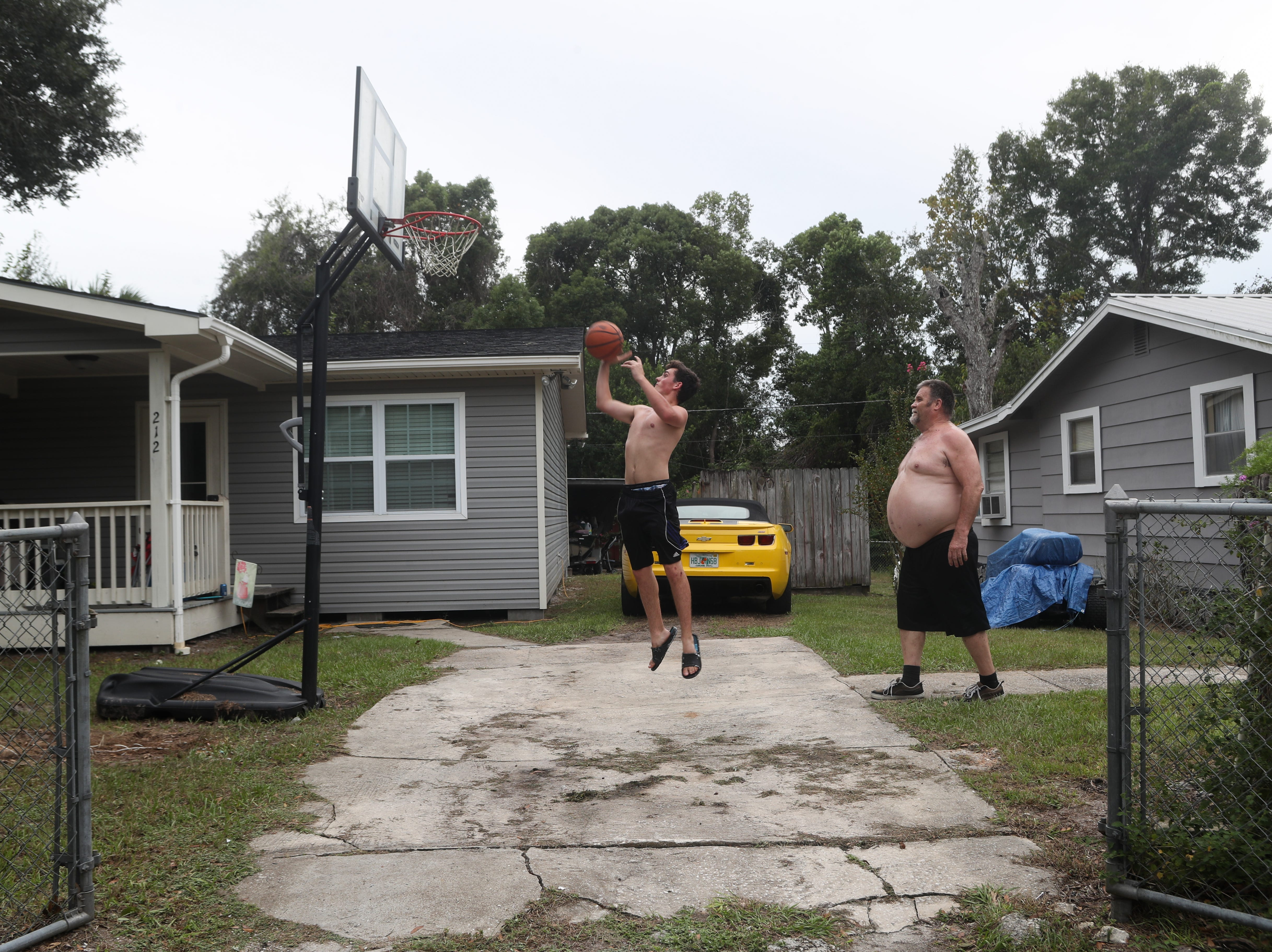 """""""I've been here 61 years and I ain't never left,"""" said John Silva as he plays basketball with his son Seth Silva, 17, in their front yard on Fourth Street in Apalachicola, Fla. Tuesday evening, Oct. 9, 2018. The family was not planning to leave their home despite a mandatory evacuation order for all of Franklin County given on Tuesday morning."""