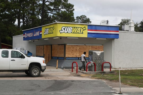 The Express Lane gas station and Subway in Carrabelle, Fla. is boarded up as customers get their final supplies ahead of Hurricane Michael Tuesday, Oct. 9, 2018.