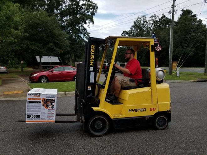 Ace Hardware Store Manager Matt Crockett drives a forklift to help a customer load the last generator in the store Tuesday afternoon.
