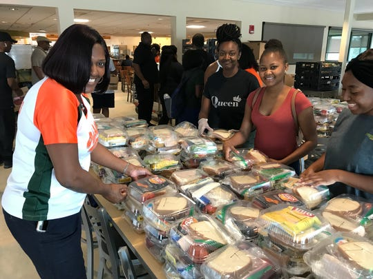 Rebecca Brown, assistant vice president for finance and administration at Florida A&M University, left, helps prepare boxed lunches for students.