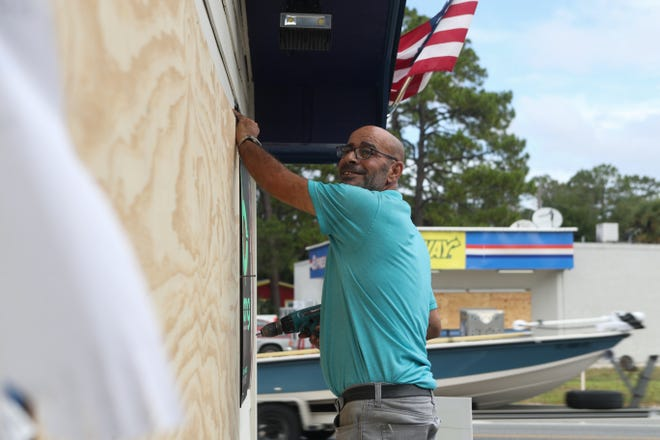 Akef Elkhatteeb, manager of Hometown Deli in Carrabelle, Florida, boards up the windows of the gas station Oct. 9, 2018, in preparation for Hurricane Michael.