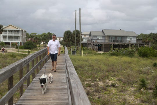 Roger Malone of Decatur, Tenn. walks towards the beach on St. George Island ahead of Hurricane Michael Tuesday, Oct. 9, 2018. Malon and his partner, Angela Ferguson, were vacationing with family on the island and as of Tuesday, the group chose not the evacuate despite a mandatory evacuation order for all of Franklin County.