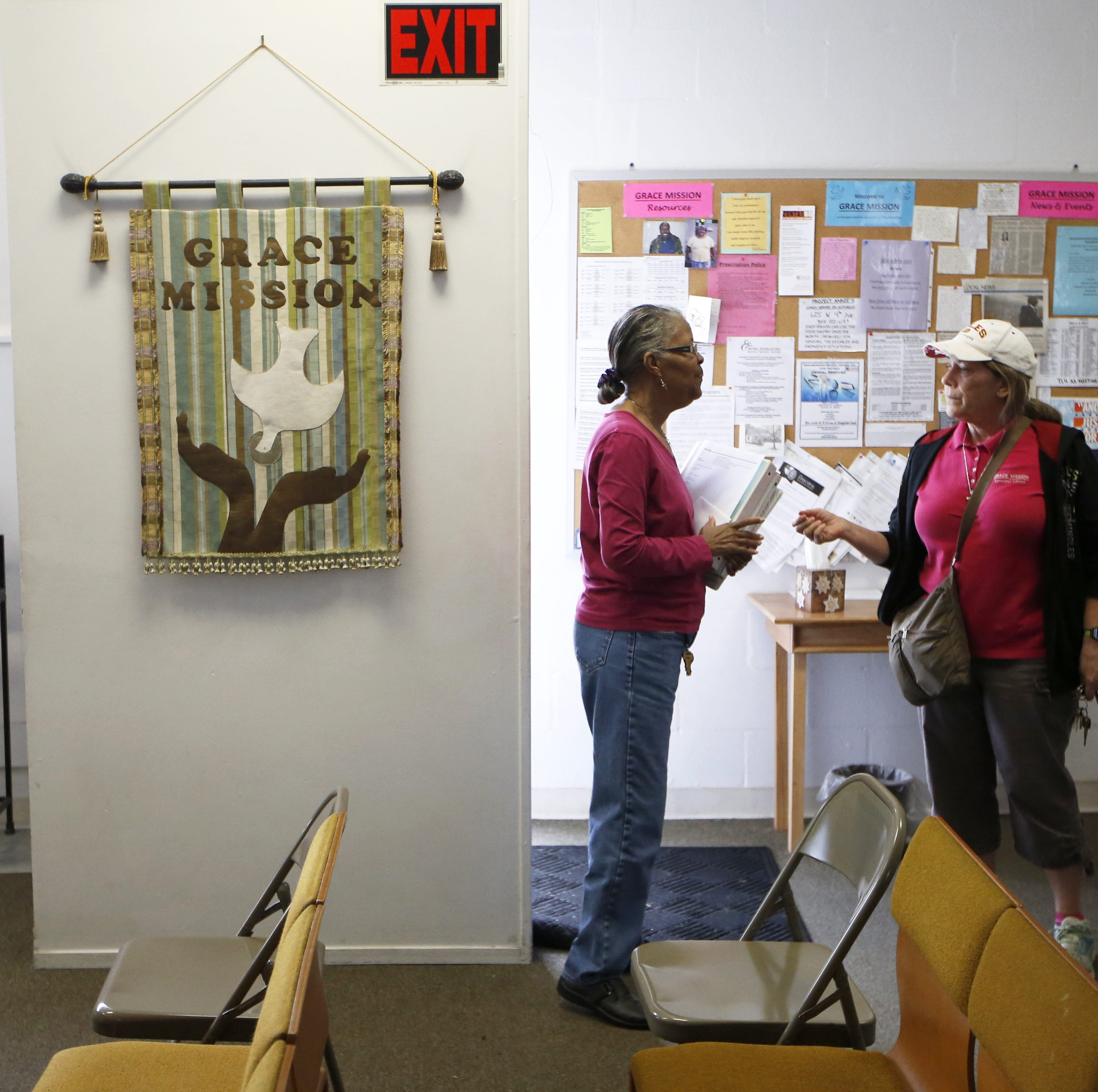 Administrative Assistant Delois Brown, left, and Pastor Amanda Nickles chat about a client at the front door of Grace Mission. Despite the approaching hurricane Nickles is planning a food giveway for Saturday, Oct. 13