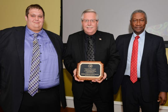 Corey Compton, left, and George Seliga, of Aycock Funeral Homes, with CACG President Neville Lake at the Fall Dinner Ball.  Aycock Funeral Homes received a Community Partner Award for its long-term support of the Caribbean American Cultural Group.
