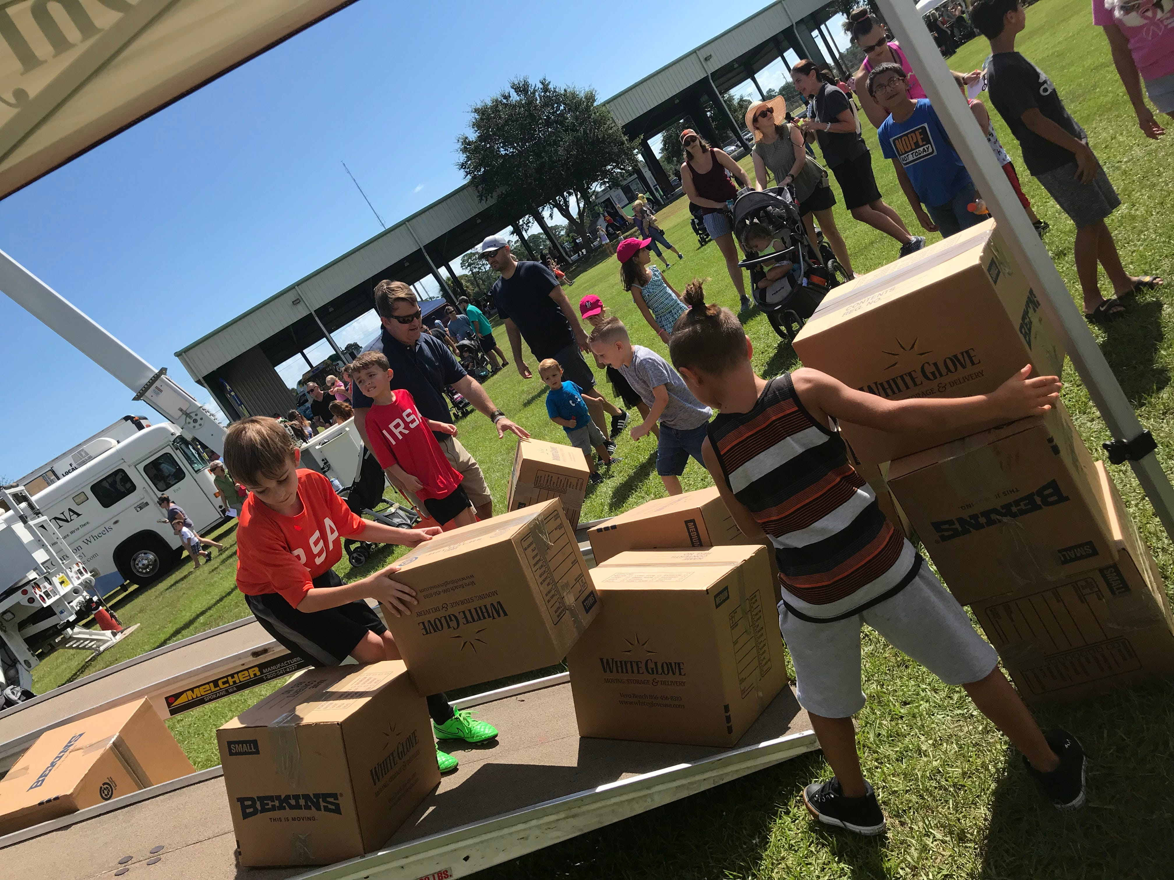 Children help haul boxes from the the boxes at White Glove Moving truck.