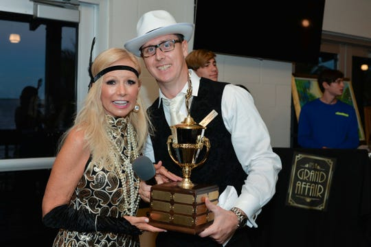 Grand Sponsor Susan Maxwell is presented with a trophy by Elev8Hope Board Member Brian Moriarity.