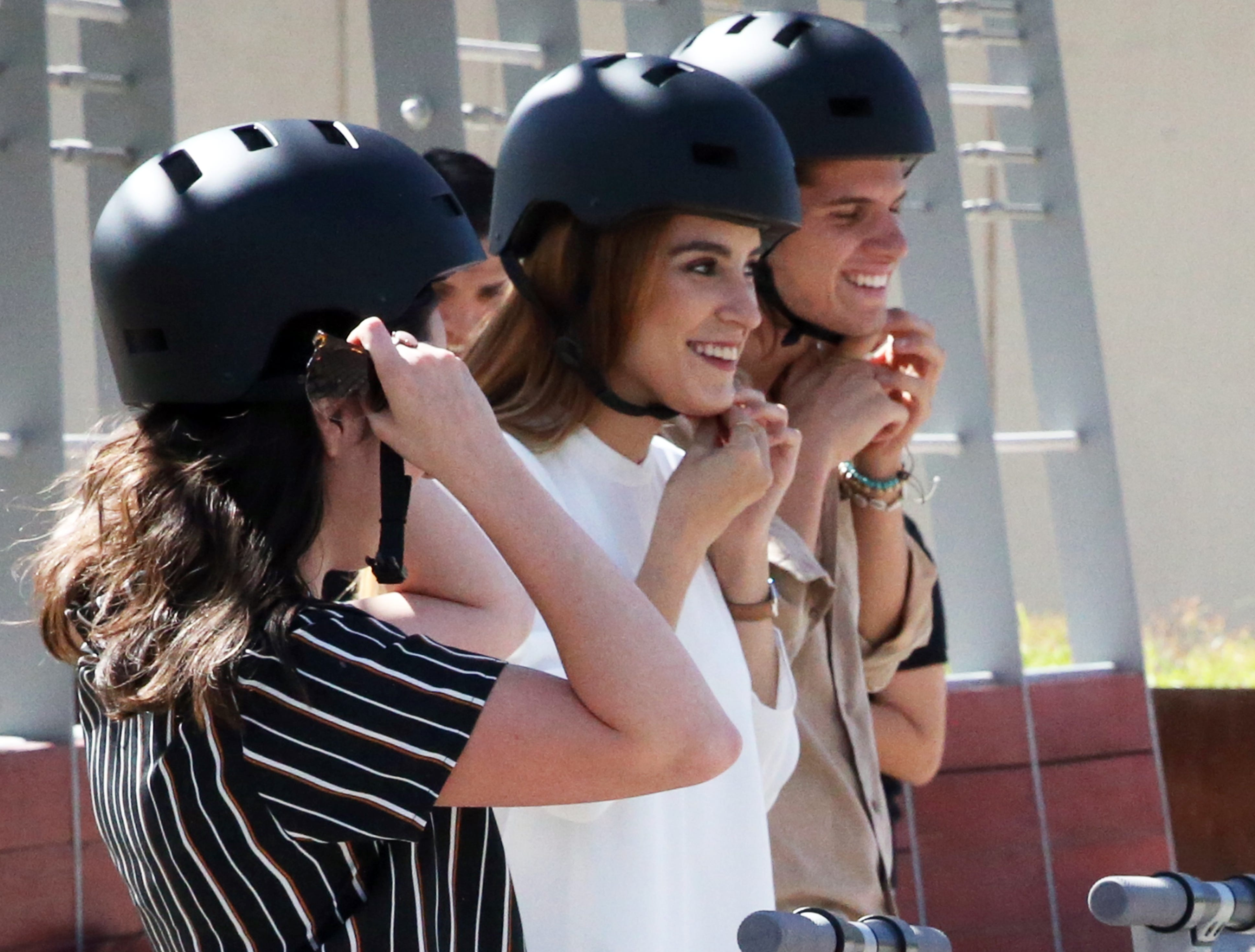Monca Valdez, center, and others put on helmets during a demonstration on the new Glide scooters Tuesday in downtown El Paso.