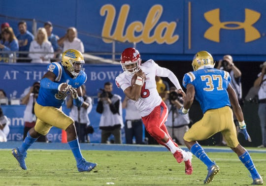 Fresno State quarterback Marcus McMaryion runs between UCLA defensive lineman Osa Odighizuwa, left, and defensive back Quentin Lake at the Rose Bowl on Saturday, September 15, 2018.