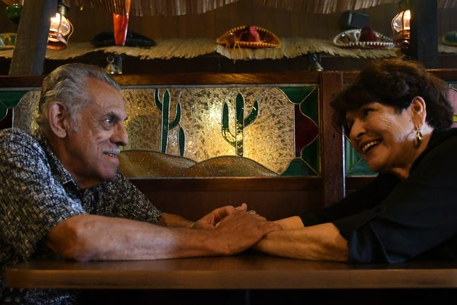 Alicia and Gilberto Cortes embrace in front of one of the restaurant's stained glass windows, a cactus representing Alicia's Arizona desert roots.