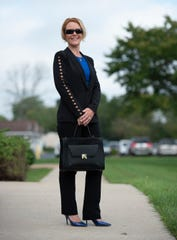 Laura Rimmer wears an Elie Tahari Wendy jacket in black with diamond cutouts down the sleeves; Calvin Klein sleeveless ruched top in electric blue; black pencil dress pants from The Limited; and BCBG electric blue heels.