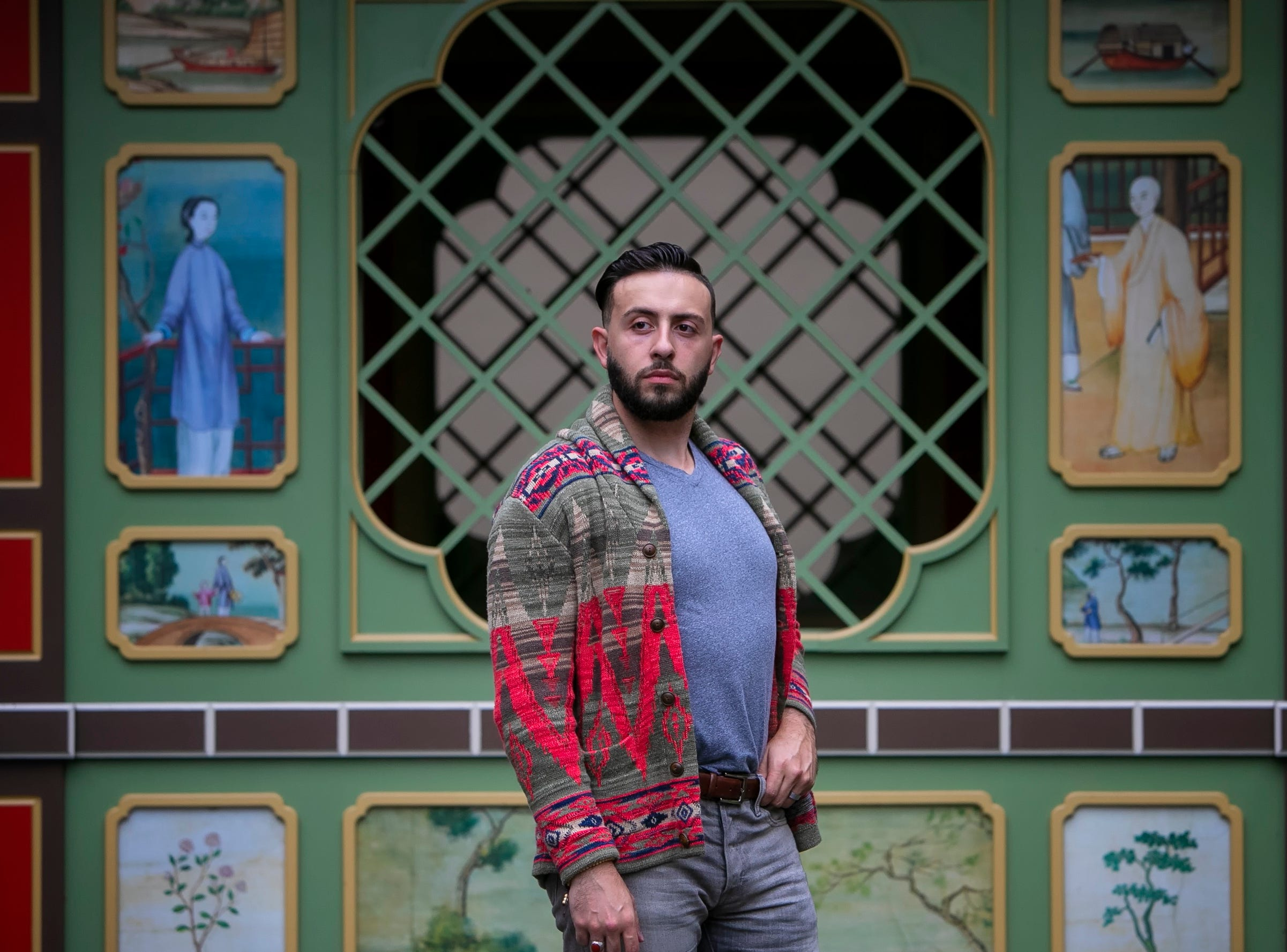 Torrey Malek wears a Ralph Lauren Polo patterned shawl cardigan and stonewashed jeans with a United by Blue heather grey T-shirt and Metro Charm brown leather boots.