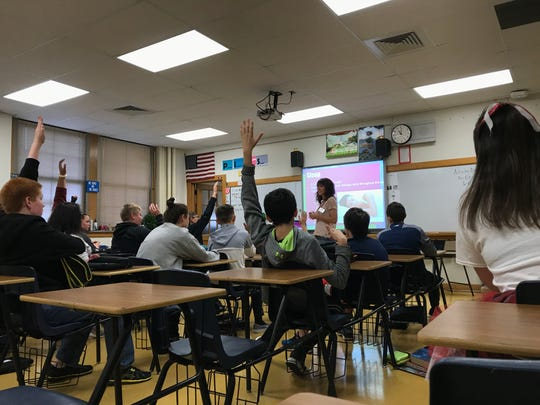 Eighth grade students raise their hands to answer a question Holly Fox asked about cancer during a presentation Oct. 5 at P.J. Jacobs in Stevens Point.