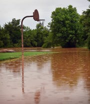 A basketball court on the west side of Lucy Park is under water as the Wichita River overflows its banks in the area.