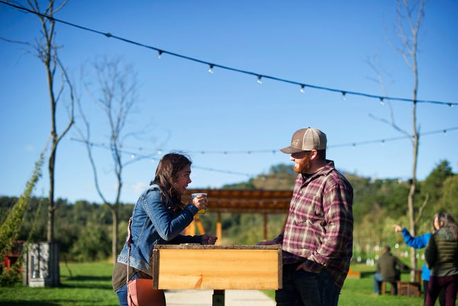 In this Sept. 28, 2018, photo, Michelle LaCasse, left, and Lucas Leverty, right, enjoy a beer at Ecker's Apple Farm in Trempealeau, Wis. Family-owned since its inception in 1945, Ecker's has looked for ways to push beyond traditional orchard offerings in the past few years, from hosting weddings to running yoga classes to making their own cider.