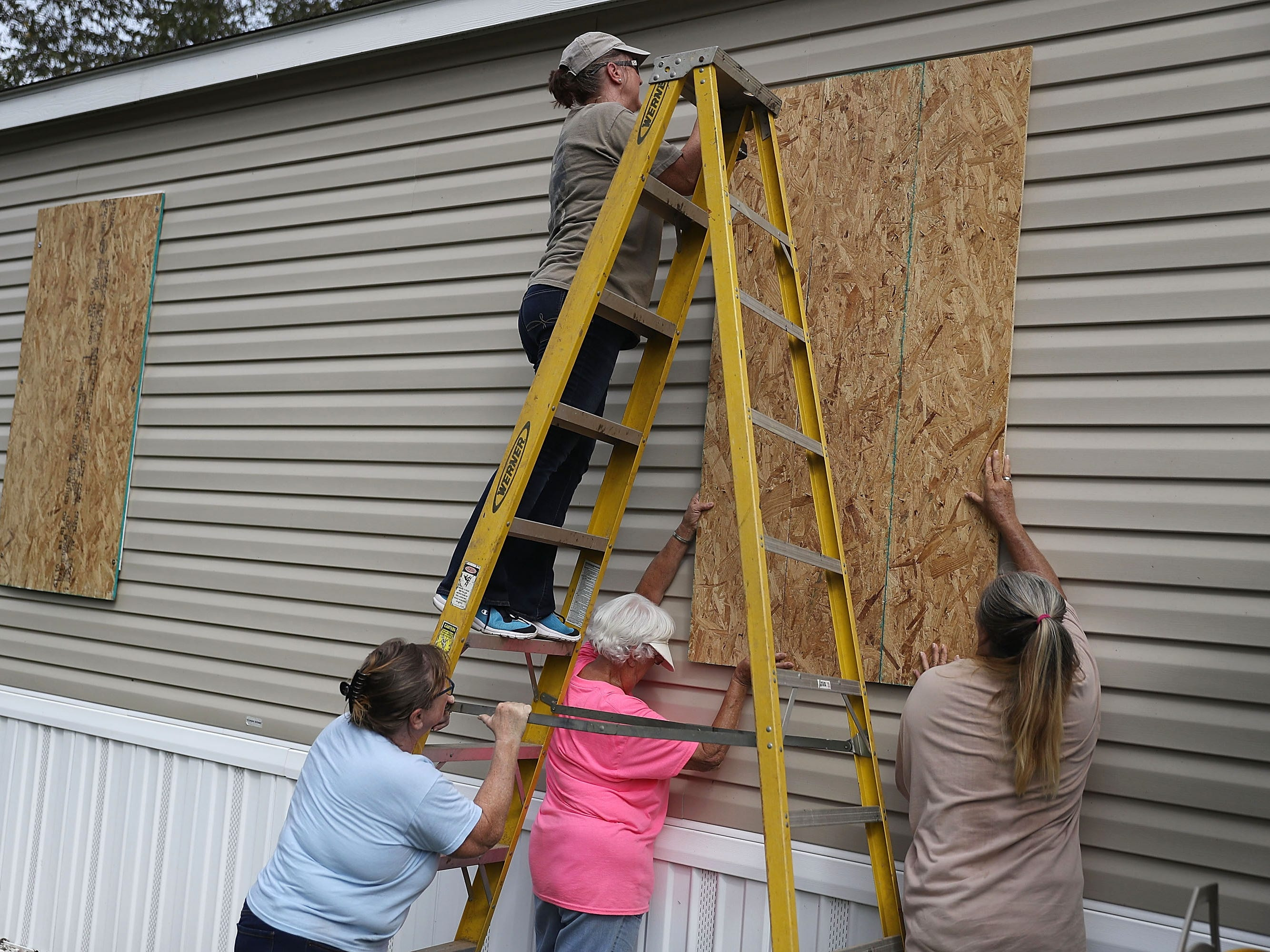 Linda Collins (on ladder) is assisted by friends as she places plywood over the windows of her home in preparation for the arrival of Hurricane Michael on Oct. 9, 2018 in Port St. Joe, Fla.