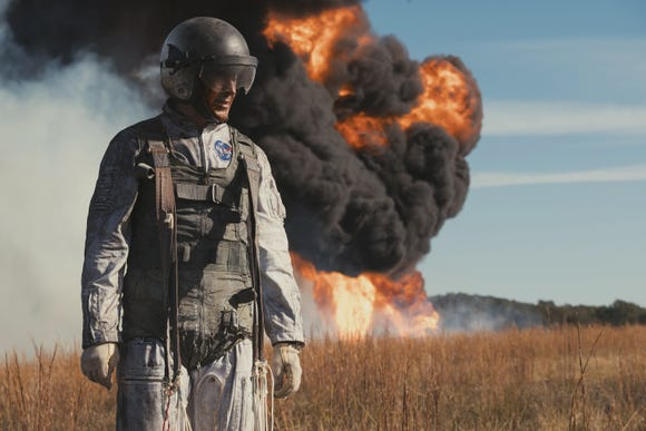 "Neil Armstrong (Ryan Gosling) narrowly escapes his lunar training vehicle before it crashes and burns in ""First Man."""