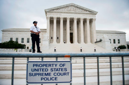 Police guard the Supreme Court on the first day that Justice Brett Kavanaugh heard oral arguments in Washington on Oct. 9.