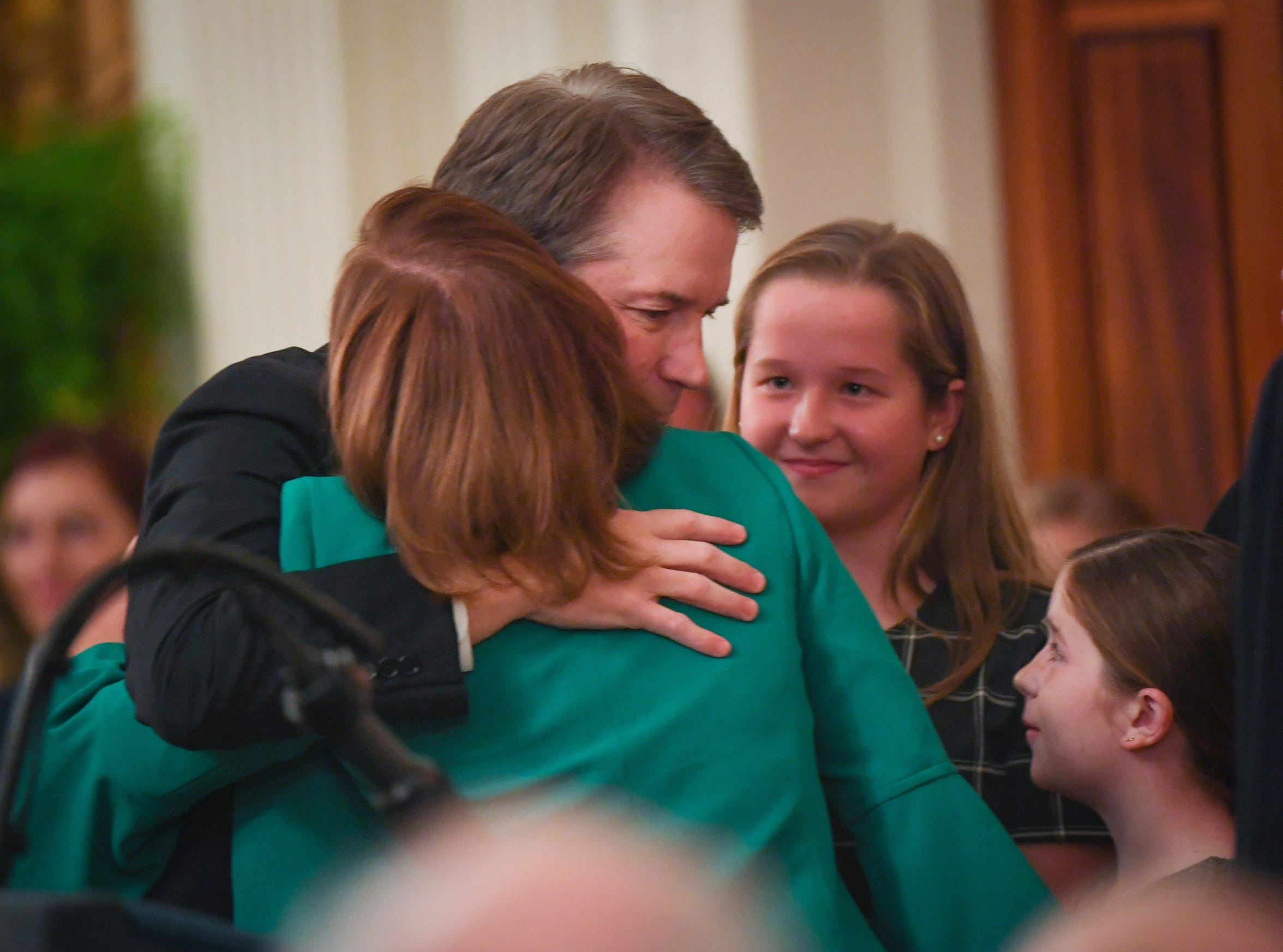Justice Brett Kavanaugh hugs his wife Ashley Kavanaugh alongside their daughters Liza Kavanaugh and Margaret Kavanaugh during the ceremony.