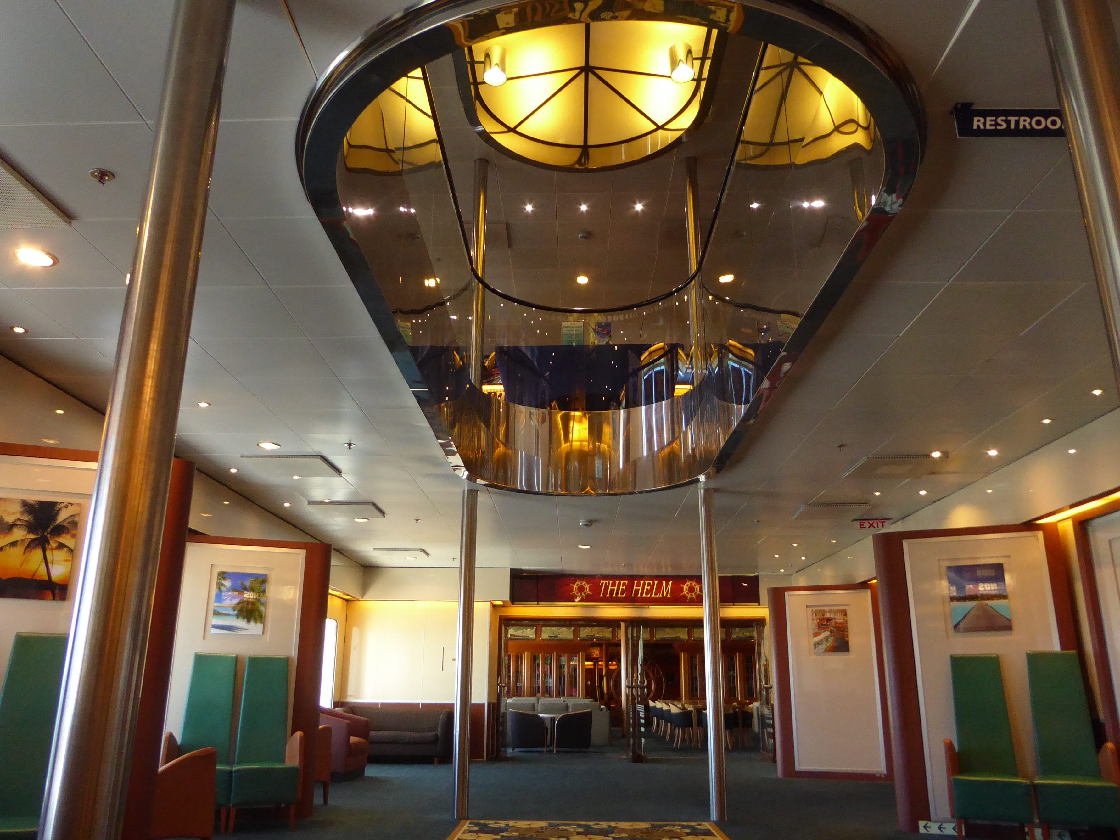 A gallery that is open to the deck above leads aft from the shops to The Helm, a library, card room and meeting room.