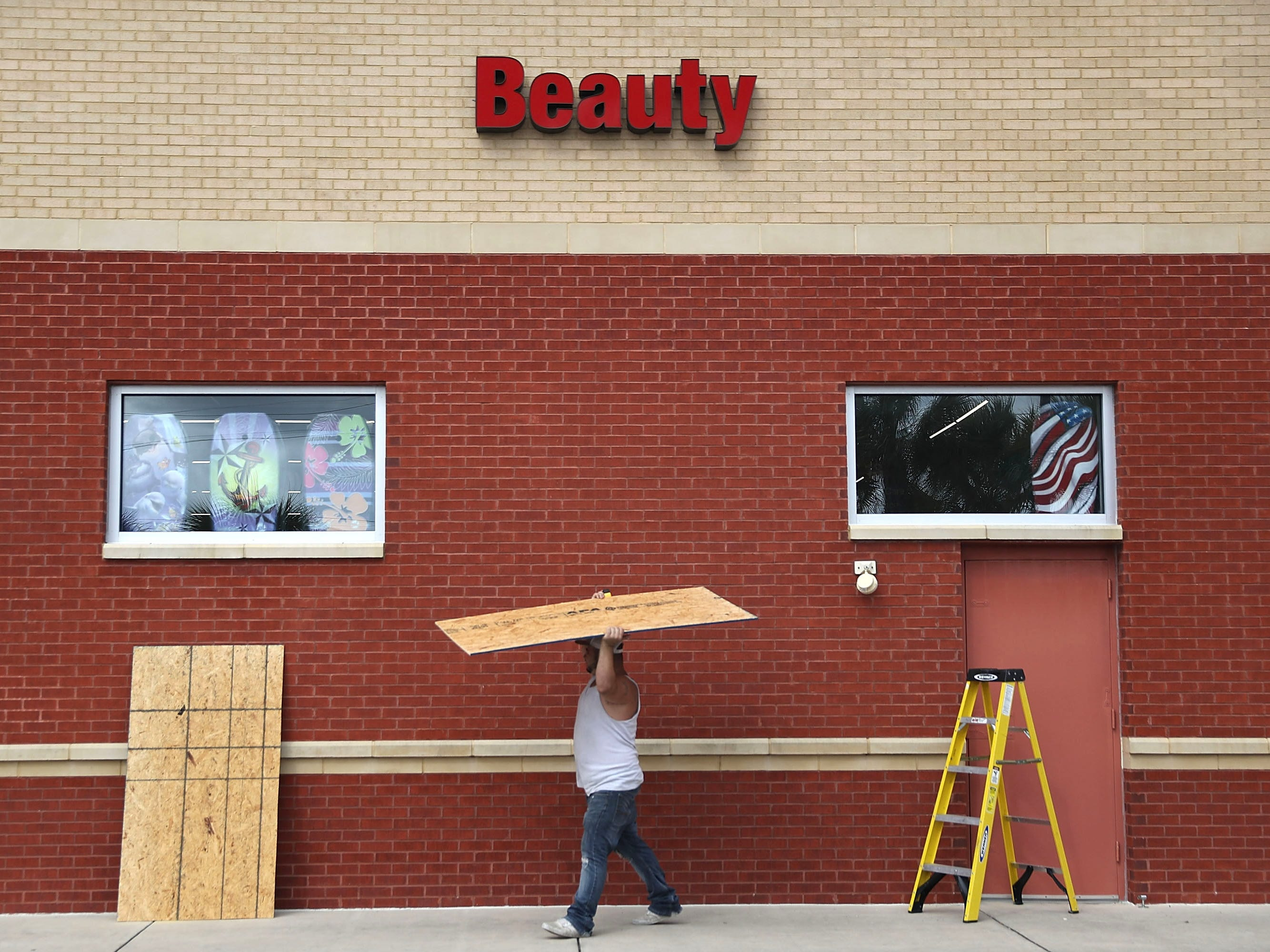 Bill Geiger works on placing plywood over the windows of a CVS store as he prepares it for the arrival of Hurricane Michael on Oct. 9, 2018 in Port St. Joe, Fla.