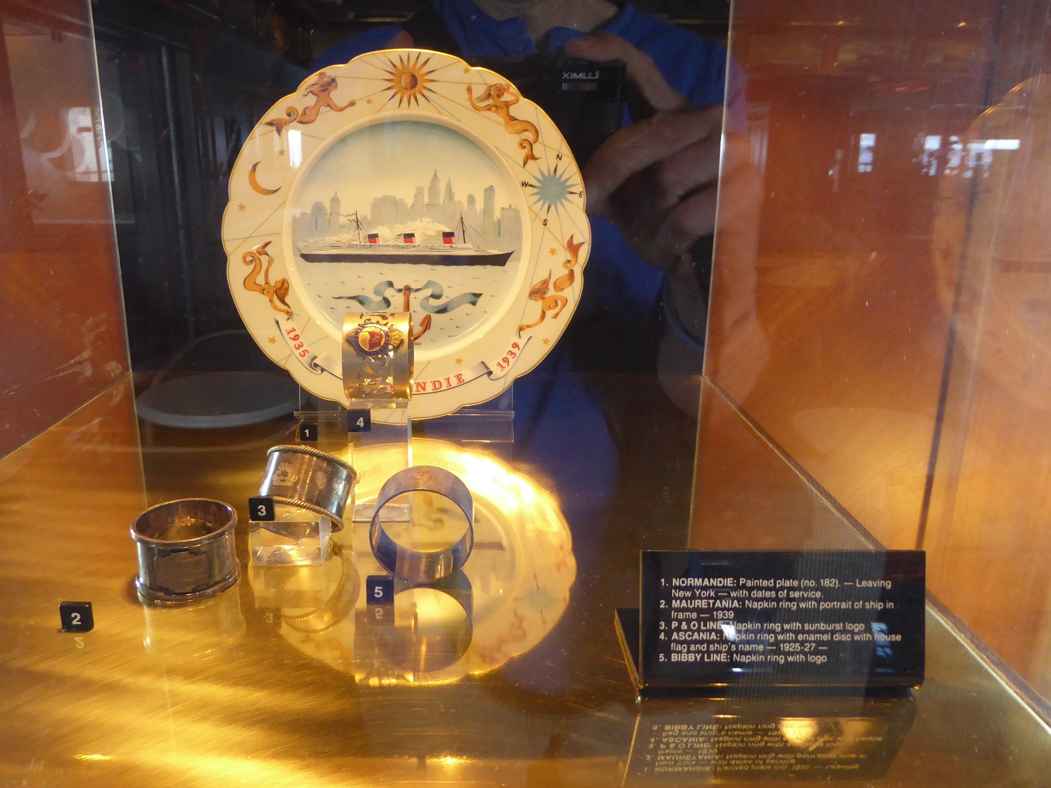 The Helm has vitrines filled with ocean liner artifacts, such as this commemorative plate from the Normandie and napkin rings from various British liners.