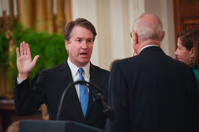 Newly confirmed Supreme Court Justice Brett Kavanaugh is sworn-in by retired Supreme Court Justice Anthony Kennedy during the ceremonial swearing-in held in the East Room of the White House in Washington.