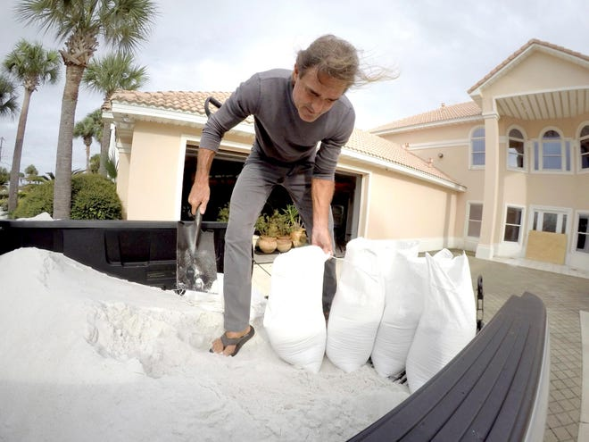 Rick Johnson fills sand bags on Oct. 9, 2018 at his Okaloosa Island home in Fort Walton Beach, Florida,  in preparation for Hurricane Michael.