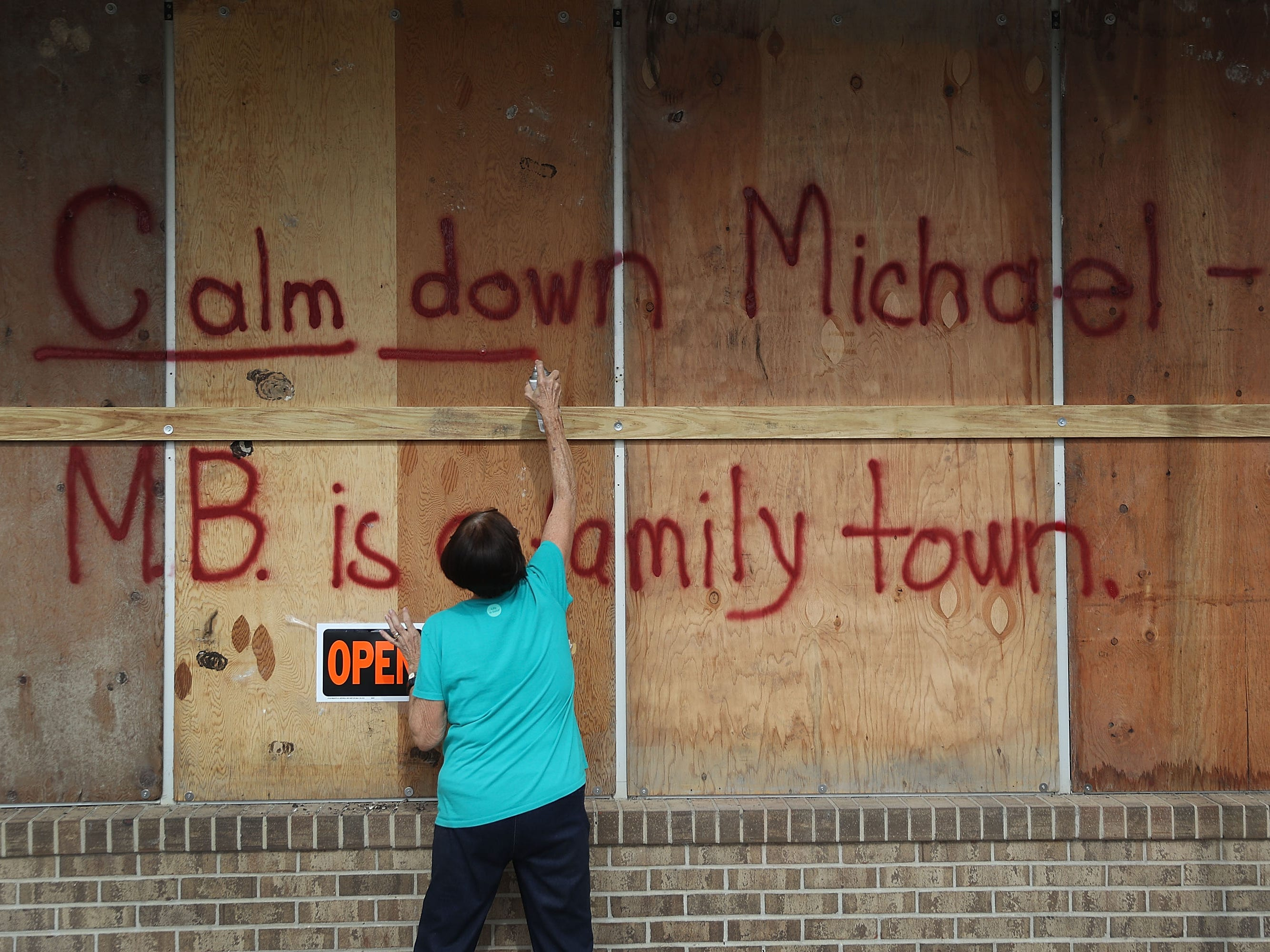 "Carol Cathey spray paints the words ""Calm down Michael"" on the plywood over her daughter's business in preparation for the arrival of Hurricane Michael on Oct. 9, 2018, in Mexico Beach, Fla."