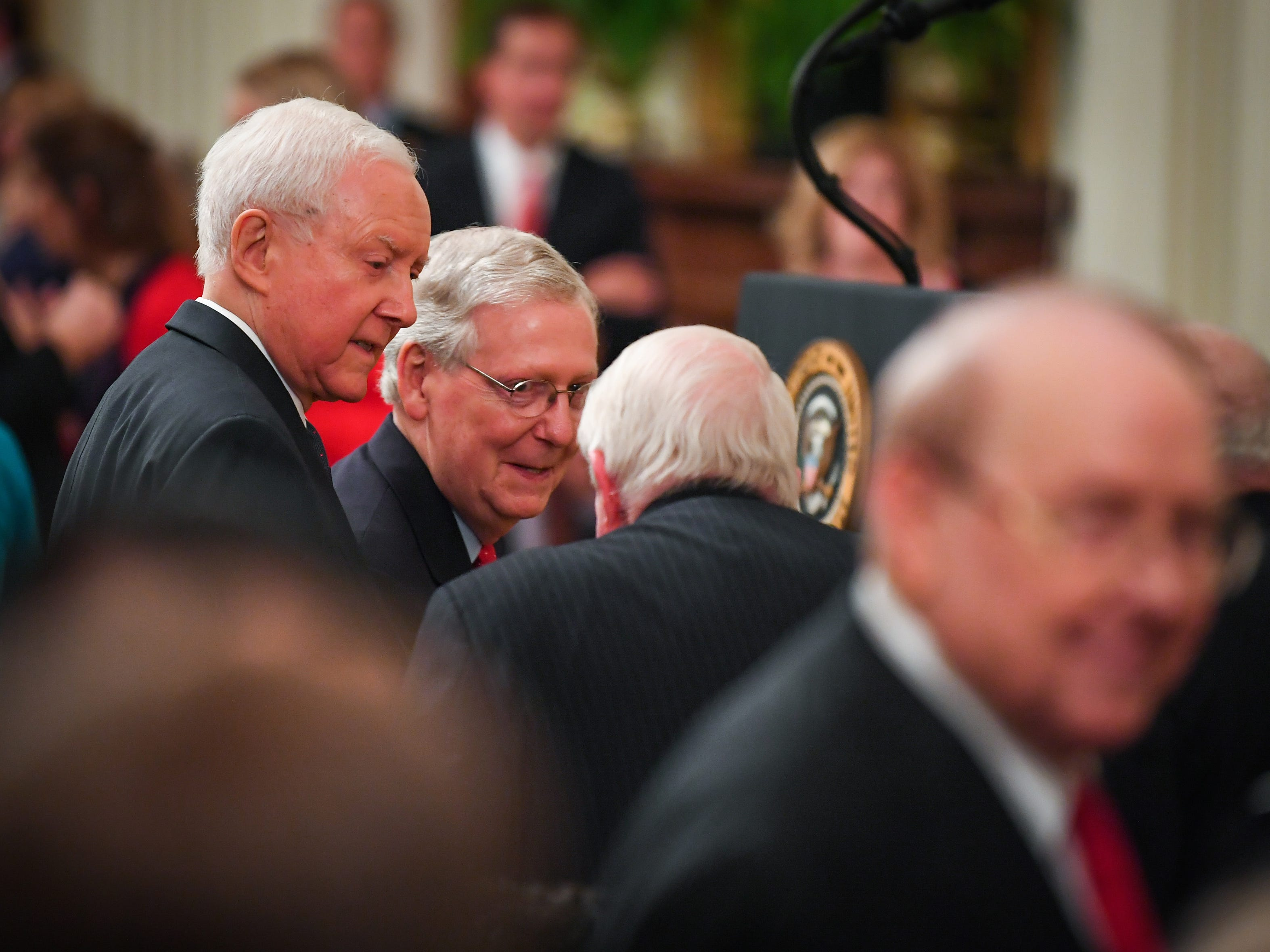 Senate Majority Leader Mitch McConnell and Senator Orrin Hatch, the senior member and former Chairman of the Senate Judiciary Committee, left, look on during the ceremony.