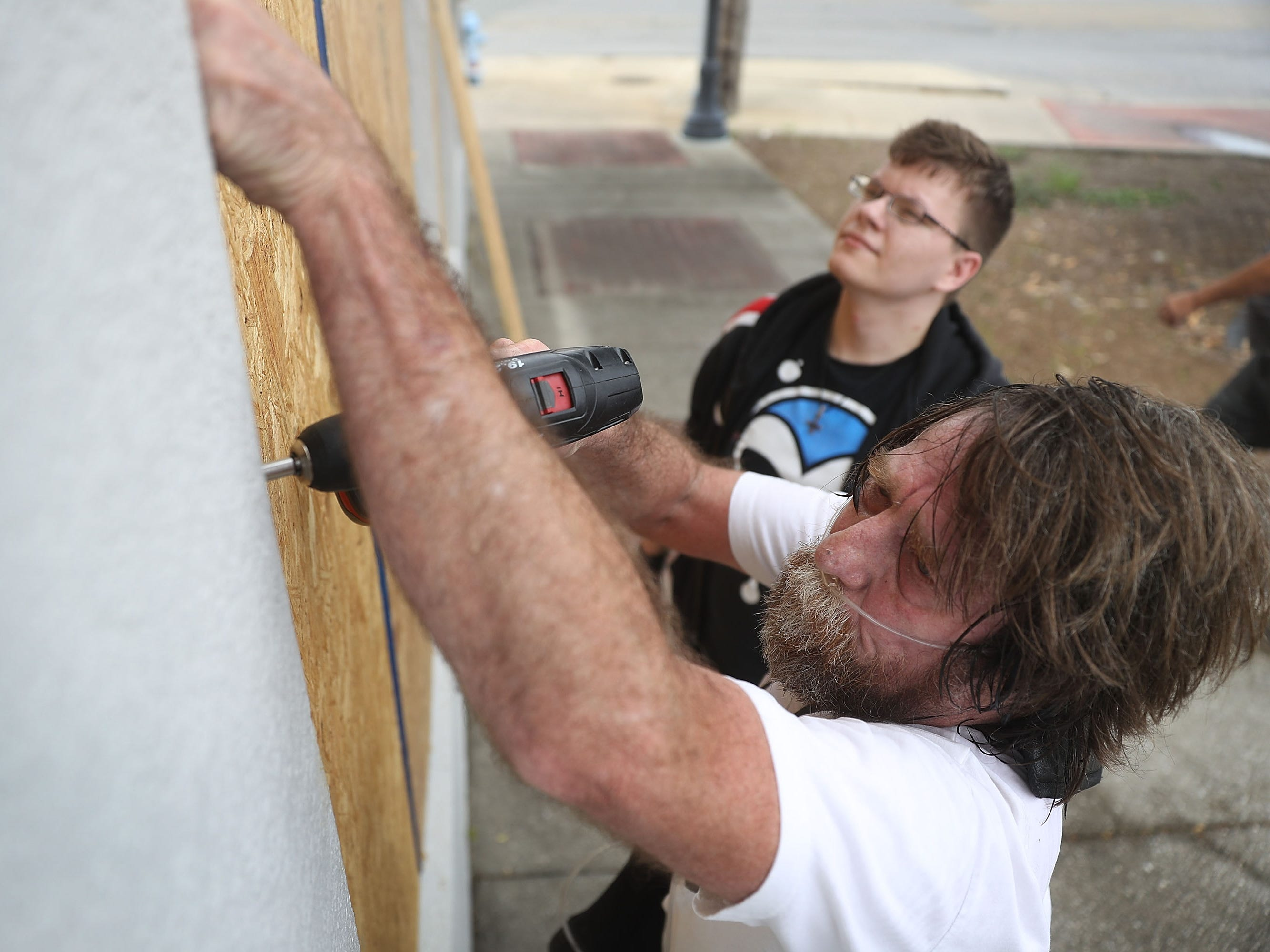 PORT ST. JOE, FL - OCTOBER 09:  Al Smith and Paul Potts (L-R) put plywood over the windows of a building as they prepare it for the arrival of Hurricane Michael on October 9, 2018 in Port St. Joe, Florida. The hurricane is forecast to hit the Florida Panhandle at a possible category 3 storm.