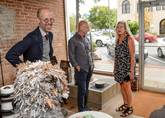 John Frampton, left, and Clay Martin, owners of Bark, a dog boutique store in downtown Anderson, talk with Stephanie Garrett. Garrett came by to talk about the Fur Ball, a fundraiser for the Anderson County Humane Society.