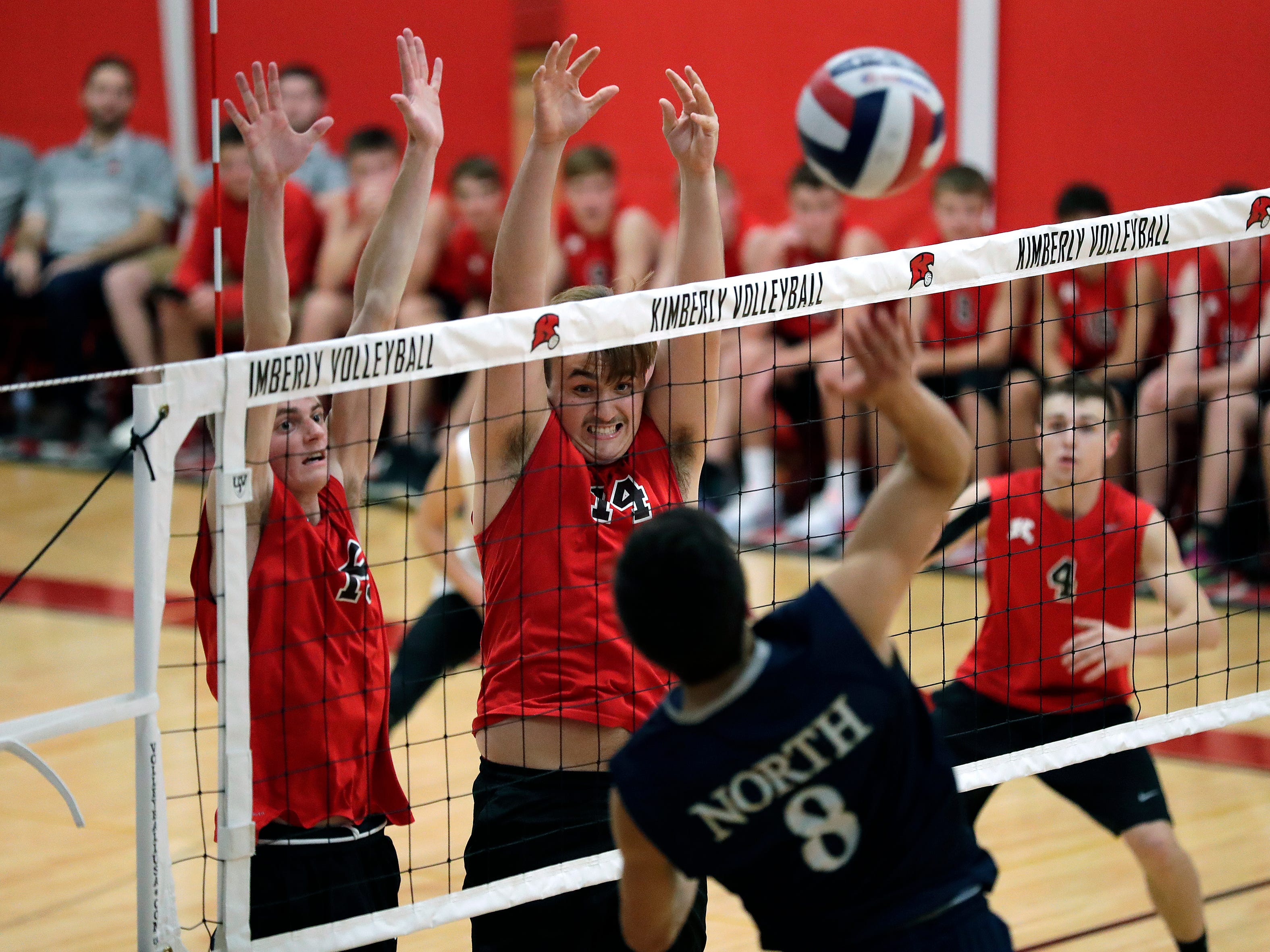Kimberly High School's James Vanevenhoven (15) and Luke Chevalier (14) defend against Appleton North High School's Andrew Woodbury (8) during their boys volleyball match Tuesday, Oct. 9, 2018, in Kimberly, Wis. 