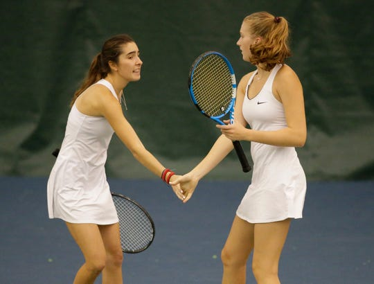 Xavier's No. 1 doubles team of Ellie Macksood, left, and Lily Anne Van Ye celebrate a point during the sectional meet in Kohler on Oct. 3.