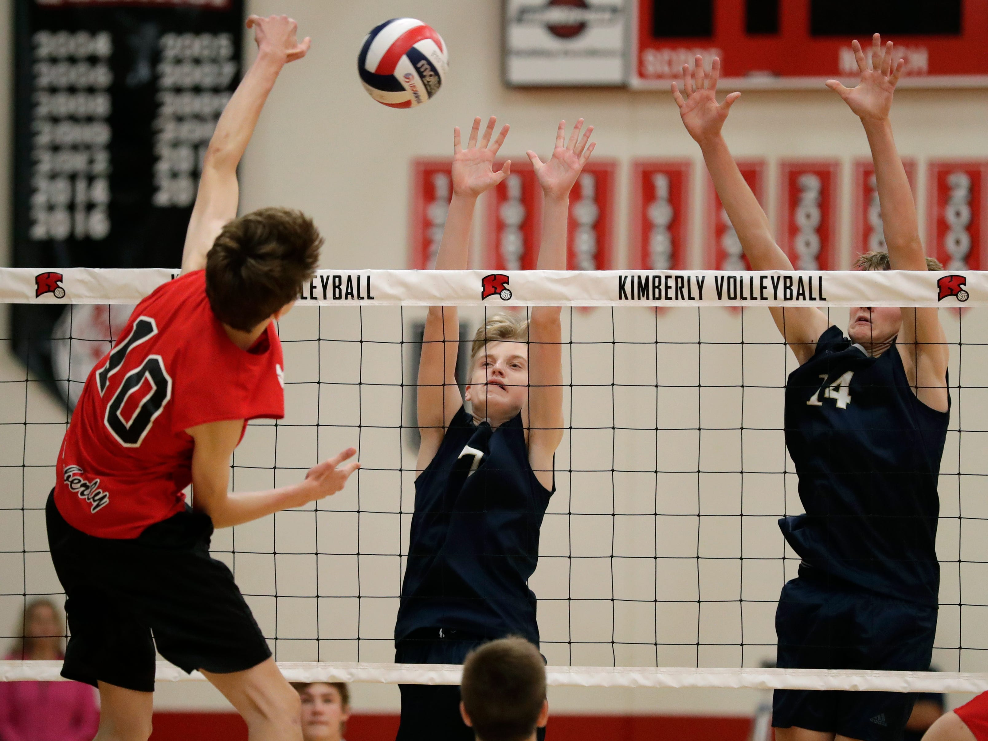 Appleton North High School's Chase Haferman (7) and Charlie Figy (14) defend against Kimberly High School's Landon Krause (10) during their boys volleyball match Tuesday, Oct. 9, 2018, in Kimberly, Wis. 