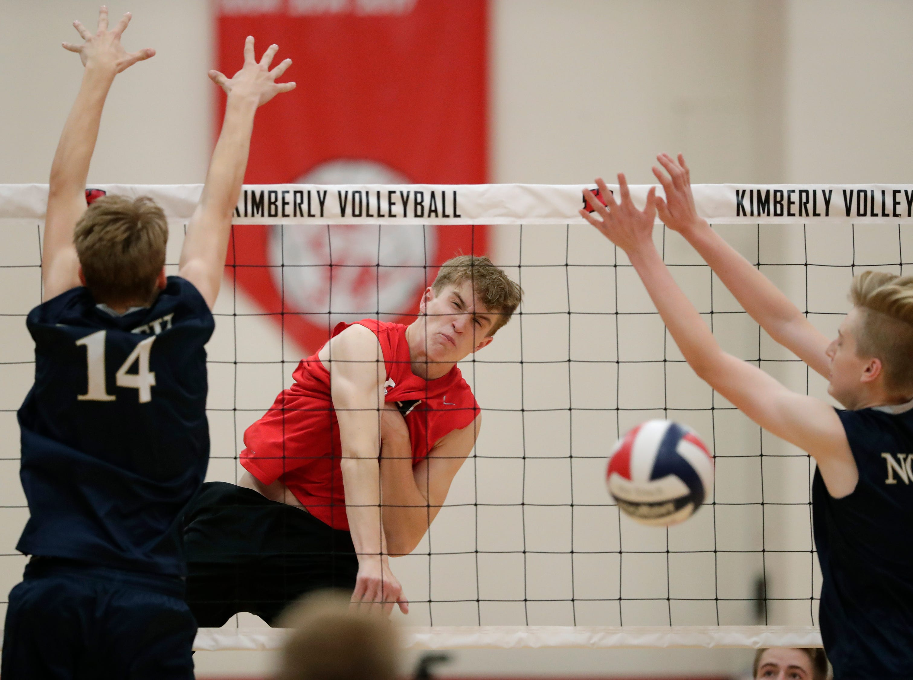 Kimberly High School's Tommy Clausz (9) spikes the ball against Appleton North High School's Charlie Figy (14) and Chase Haferman (7) during their boys volleyball match Tuesday, Oct. 9, 2018, in Kimberly, Wis. 