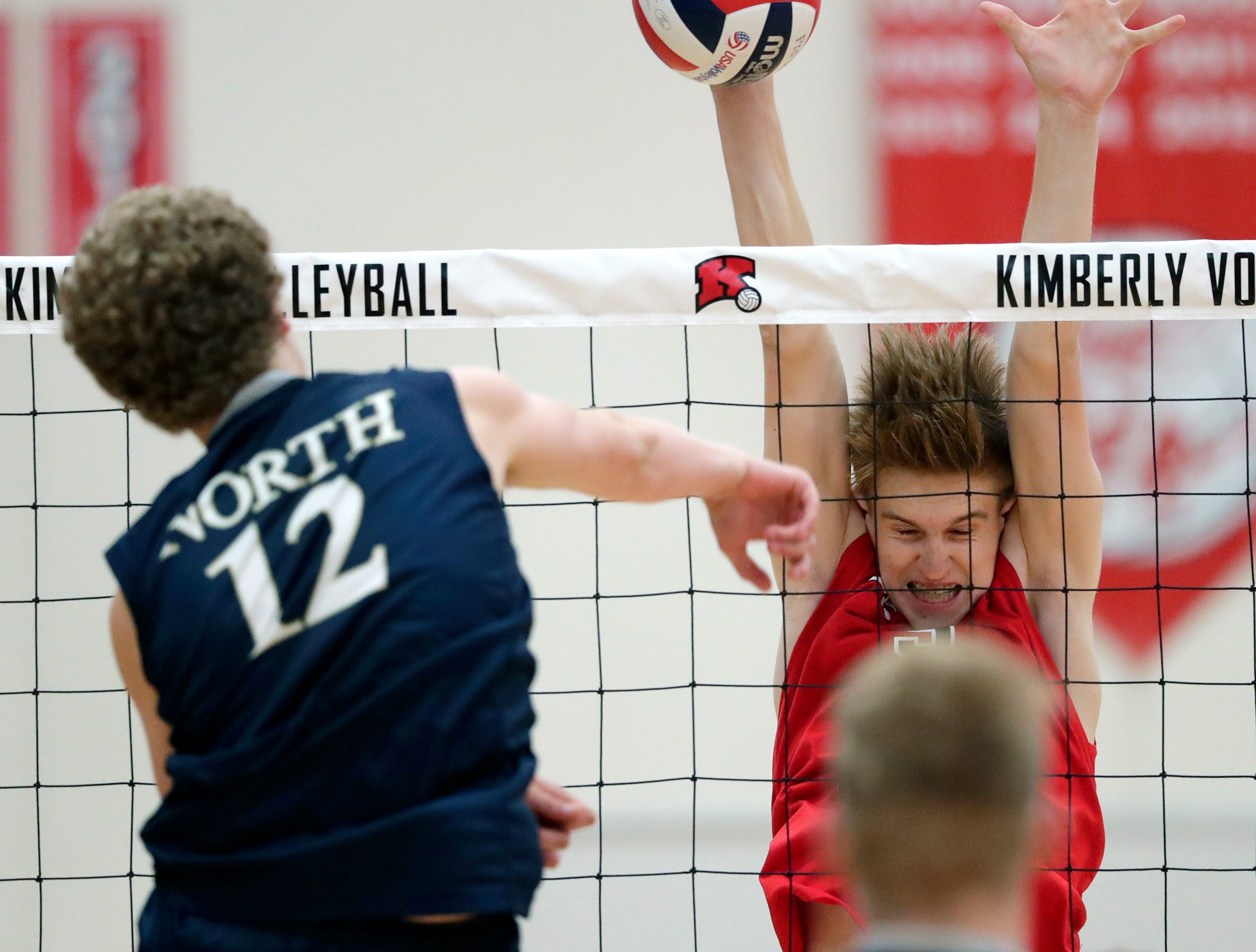 Kimberly High School's Tommy Clausz (9) blocks a shot against Appleton North High School's Alex Zarneke (12) during their boys volleyball match Tuesday, Oct. 9, 2018, in Kimberly, Wis. 