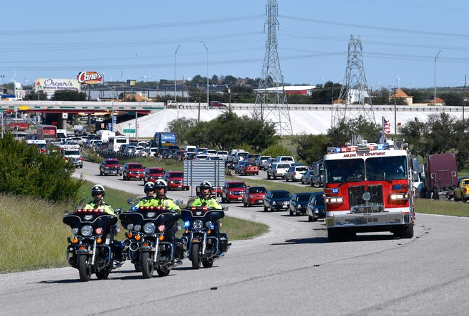 A procession of fire trucks, police and other first responders travels along Ambler Avenue Wednesday, bearing the body of Abilene firefighter Michael Degering. Some motorists exited their vehicles as the procession passed to honor Degering, who was buried at the Texas State Veterans Cemetery at Abilene.