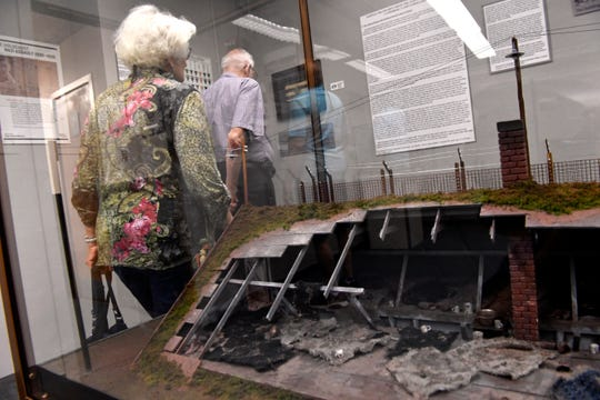 Members of the Texas Jewish Historical Society read placards and stand beside a diorama of a World War II concentration camp barracks Oct. 6 at the 12th Armored Division Museum.