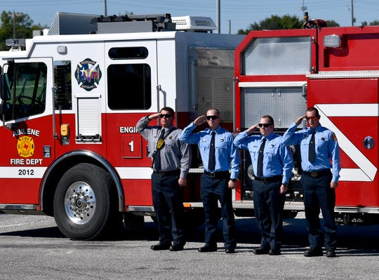 The crew of Abilene Fire Department's Engine 1 salute as they wait on the hearse bearing the body of firefighter Michael Degering to pass by on Ambler Avenue Wednesday. Firefighters, police, and others remembered Degering during a service Wednesday at Beltway Baptist Church - North.