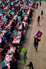 Brissa Guzman, a senior at Holland Medical School, carries a numbered sign indicating the round all the bunco players were playing Tuesday.