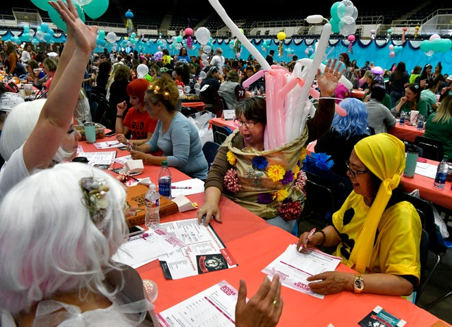 Sandra Roys (center) lifts a hand in triumph as she rolls a bunco during Tuesday's Bunco for Breast Cancer at the Taylor County Coliseum. The evening's theme was Under the Sea. Roys came dressed as a sea anemone for the fundraiser.