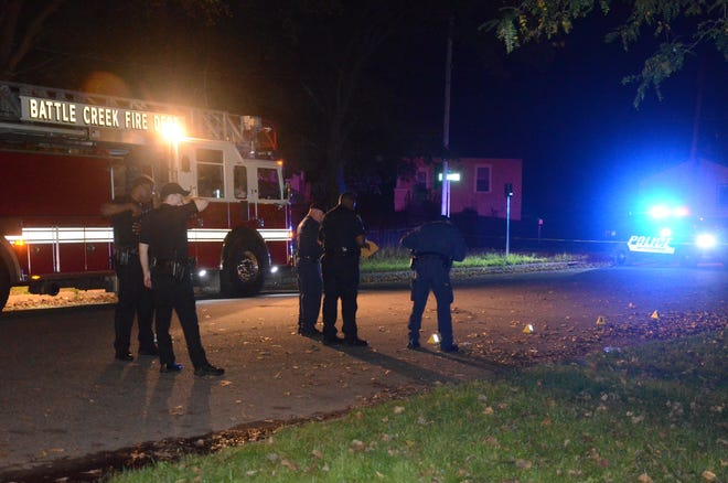 Battle Creek police search the scene of a shooting Tuesday night, Oct. 9, in Claude Evans Park in Battle Creek.
